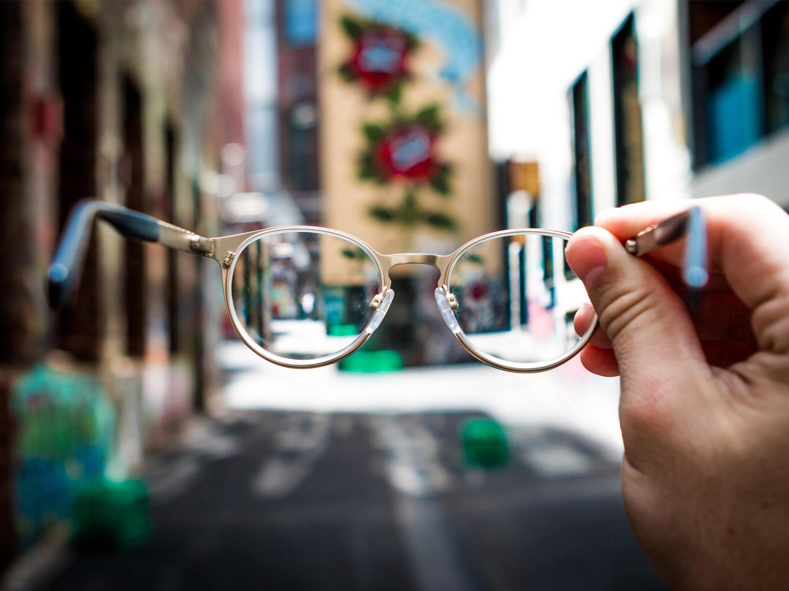 Afbeelding van een hand die een bril vasthoud