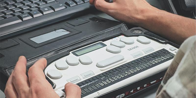 Afbeelding van 2 handen op een braille toetsenbord