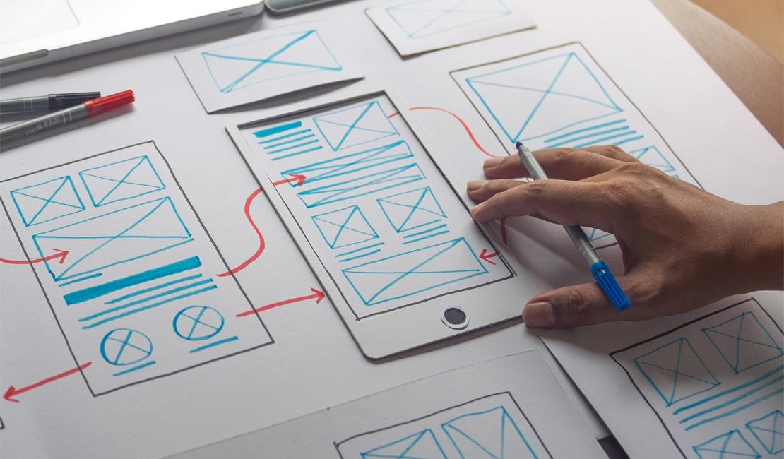Afbeelding waarop een hand te zien is die een wireframes schetst op een groot vel papier